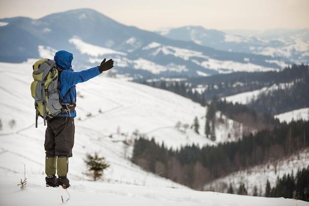 Widok z tyłu turystycznego turysty w ciepłej odzieży z plecakiem stojącym z podniesionymi rękami na górskiej polanie