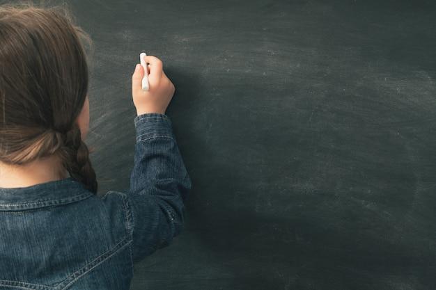 Widok z tyłu uczennicy, która ma zamiar pisać kredą na czarnej tablicy