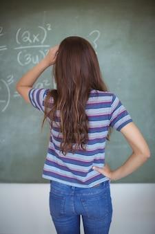 Widok z tyłu uczennicy udającej nauczyciela w klasie