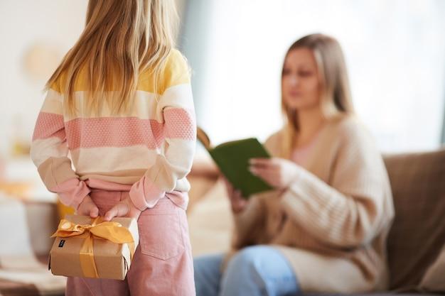 Widok z tyłu uroczej dziewczynki ukrywającej prezent dla mamy, zaskakując ją w dzień matki lub urodziny w przytulnym wnętrzu domu, skopiuj miejsce