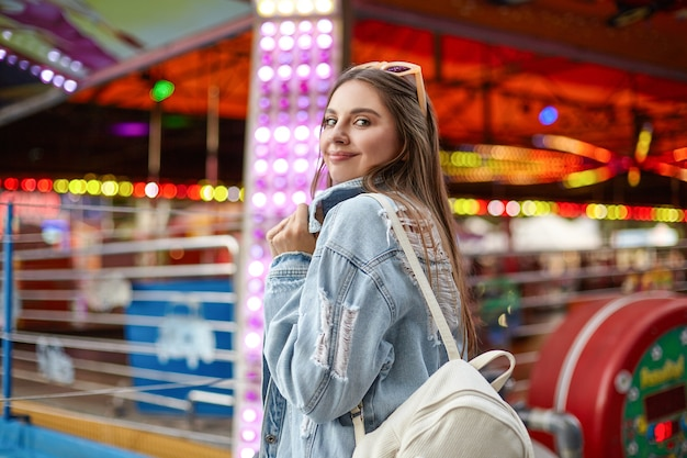 Widok z tyłu uroczej młodej brunetki w modnym dżinsowym płaszczu obracającej się z delikatnym uśmiechem, spacerującej wzdłuż atrakcji w parku rozrywki w ciepły jasny dzień