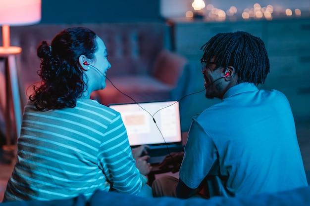 Widok z tyłu uśmiechniętej pary za pomocą laptopa i słuchawek w domu