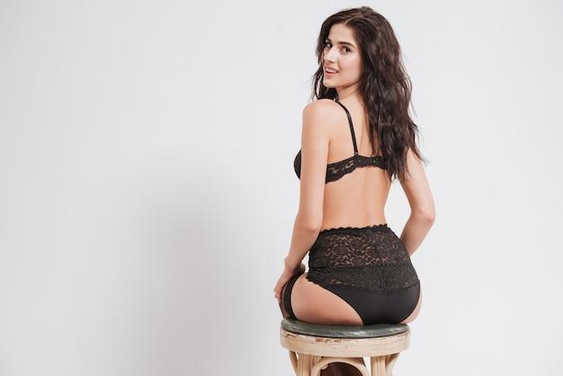 Widok z tyłu uśmiechniętej pięknej kobiety w seksownej bieliźnie siedzącej na krześle i patrzącej na przód na białym tle