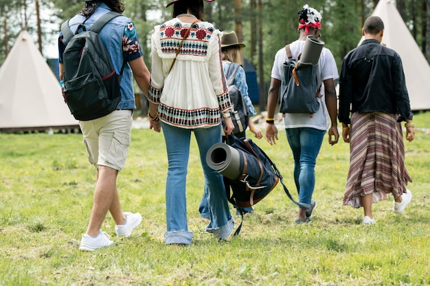 Widok z tyłu wieloetnicznych turystów w letnich strojach chodzących po trawie do namiotów podczas planowania pobytu w obozie, koncepcja festiwalu