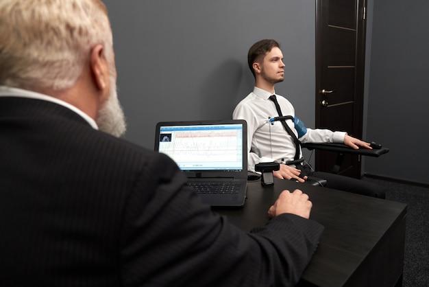 Widok z tyłu wykwalifikowanego mężczyzny w elegancki garnitur robi test kłamstwa