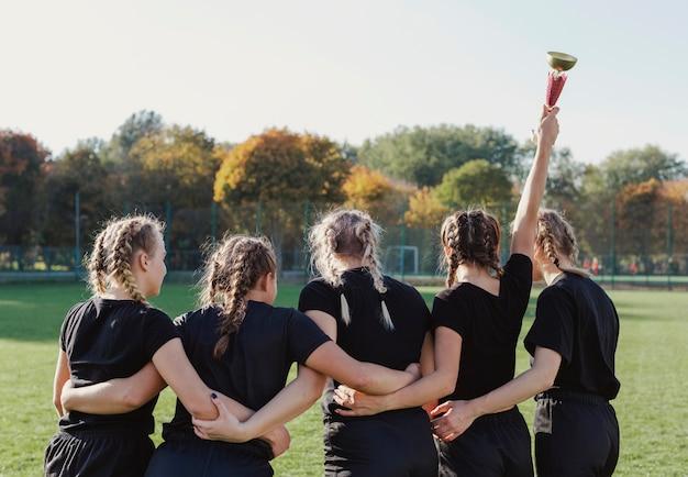 Widok z tyłu wysportowane dziewczyny wygrywające trofeum