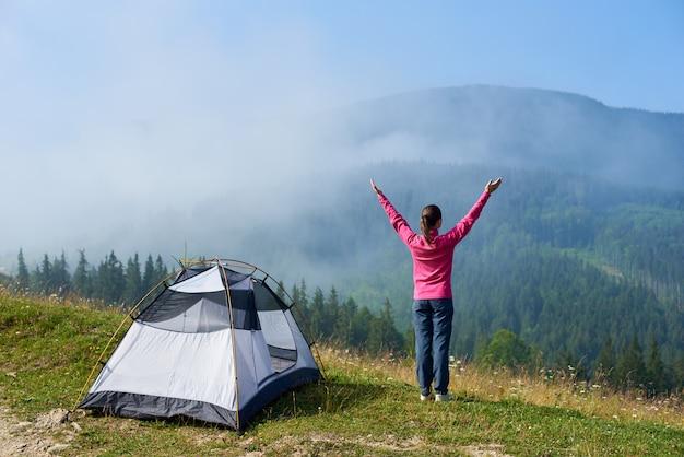 Widok z tyłu z aktywną turystyczną dziewczynę stojącą z podniesionymi rękami na wzgórzu w namiocie turystycznym, ciesząc się widokiem mgliste góry w słoneczny letni poranek słoneczny