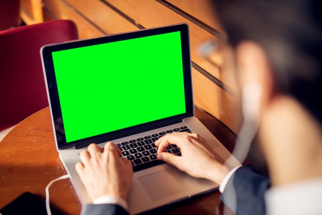 Widok z tyłu z bliska widok laptopa z pustym zielonym ekranem i rękami młodego biznesmena, odnoszącego sukcesy, stylowego, skupionego w garniturze ze słuchawkami, piszącego w kawiarni lub restauracji w pobliżu drewnianej ściany.