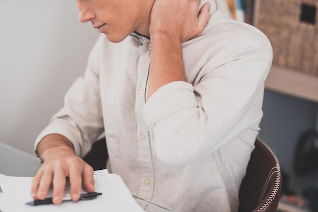 Widok z tyłu z bliska zestresowany młody człowiek dotykający dolnej części szyi odczuwający dyskomfort, cierpiący z powodu nagłego bólu z powodu siedzącego trybu życia lub długiego przepracowania komputera w nieprawidłowej postawie w domowym biurze.