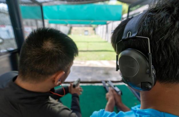 Widok z tyłu z dwóch mężczyzn strzelanie z pistoletu na cel w strzelnicy.