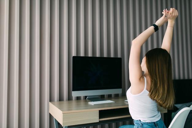 Widok z tyłu z tyłu na zrelaksowaną młodą kobietę odpoczywającą zakończoną pracę siedzącą przy biurku z rękami za głową
