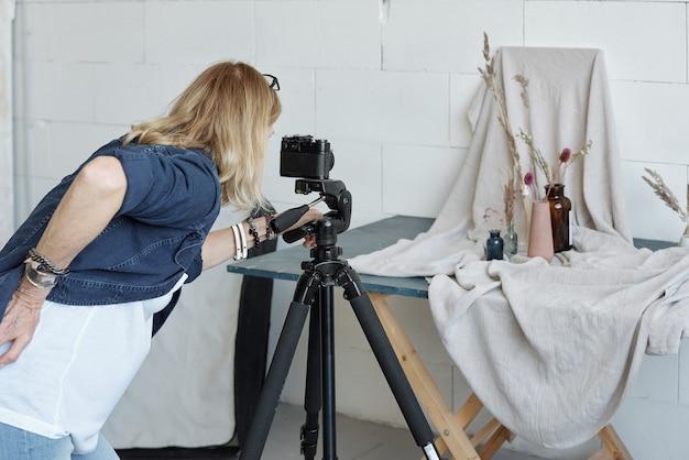 Widok z tyłu zajętej kobiety kreatywnej za pomocą aparatu na statywie podczas fotografowania kompozycji wazonu w studio