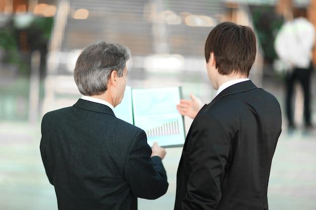 Widok z tyłu. zbliżenie partnerów biznesowych omawiających dokumenty finansowe. koncepcja biznesowa