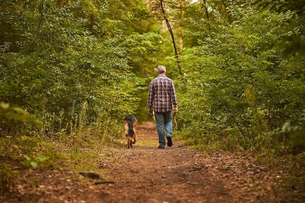 Widok z tyłu zdjęcia starszego mężczyzny idącego wraz ze swoim uroczym psem leśną ścieżką