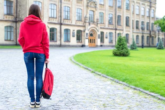 Widok z tyłu zdjęcie dziewczyny trzymając tło kampusu tornister