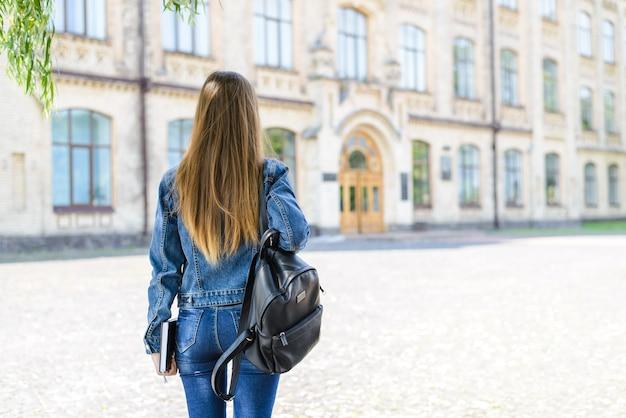 Widok z tyłu zdjęcie dziewczyny z tłem kampusu książki i torby