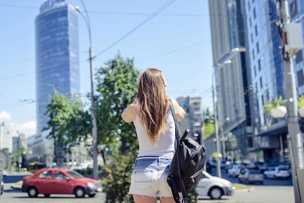 Widok z tyłu zdjęcie dziewczyny zamykające uszy rękami na tle budynków