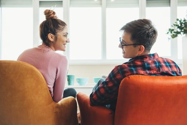 Widok z tyłu zdjęcie kaukaskiej pary leżącej w fotelu, uśmiechając się do siebie