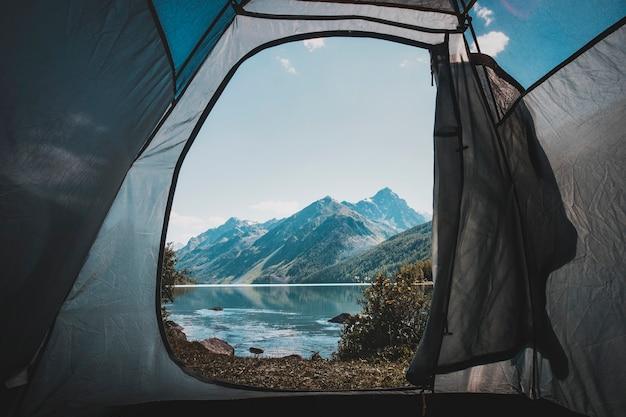 Widok z wejścia do namiotu na piękne jezioro w godzinach porannych. kemping w górach. piękny widok z namiotu. odpoczywaj na wolności. atmosferyczne zdjęcie stonowane.