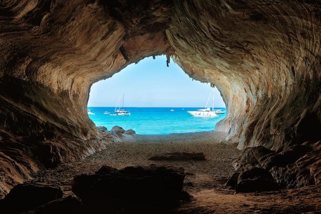 Widok z wnętrza dużej jaskini na plażę i błękitne morze. wybrzeże morza śródziemnego, sardynia, włochy.
