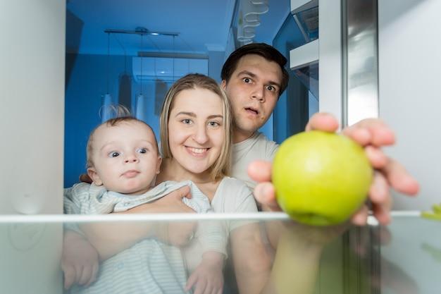 Widok z wnętrza lodówki na uśmiechniętą rodzinę szukającą czegoś do jedzenia