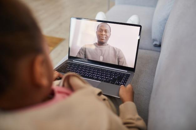 Widok z wysokiego kąta na afroamerykańską dziewczynę rozmawiającą z tatą przez czat wideo podczas dystansu społecznego, kopiowanie miejsca