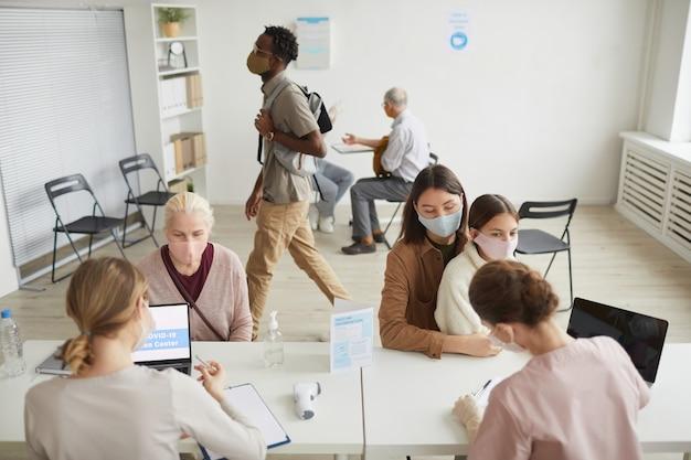 Widok z wysokiego kąta na grupę osób rejestrujących się po szczepionkę przeciw krowim w centrum szczepień, kopia przestrzeń