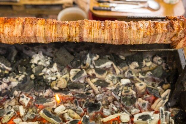 Widok z wysokiego kąta na pieczenie mięsa shawarma na rożnie nad rozżarzonymi węglami na stanowisku przygotowywania wózków spożywczych