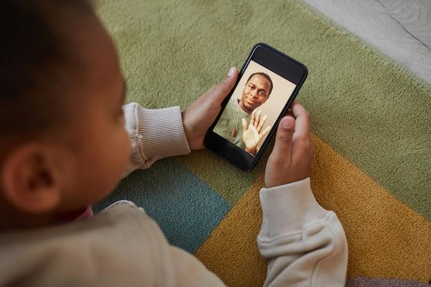 Widok z wysokiego kąta na uroczą afroamerykańską dziewczynę rozmawiającą z tatą przez czat wideo i dystans społeczny, miejsce kopiowania