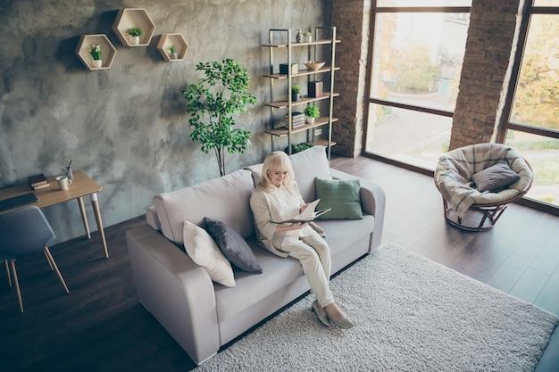 Widok z wysokiego kąta zdjęcia niesamowitej blond uroczej starszej babci dobry nastrój siedzenie wygodna sofa kanapa do czytania ulubionej powieści historycznej książka miły wolny czas salon w pomieszczeniu