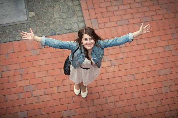 Widok z wysokiego punktu młodej uśmiechniętej kobiety wyciągającej ręce