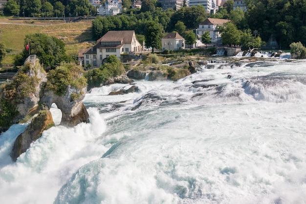 Widok z zamku laufen na rhine falls jest największym wodospadem w schaffhausen w szwajcarii. letni krajobraz, słoneczna pogoda, błękitne niebo i słoneczny dzień