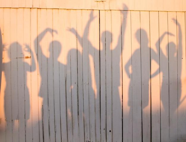 Widok zabawnej fotografii grupy przyjaciół, stwarzających pozy, tworząc cień na drewnianej ścianie.