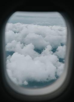 Widok zachmurzonego nieba przez okno samolotu