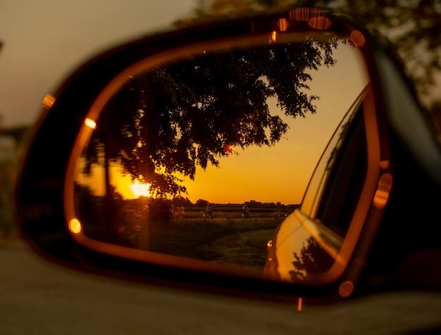 Widok zachodu słońca w lusterku samochodowym