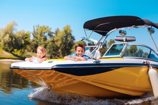 Widok zapierający dech w piersiach. radosne małe rodzeństwo siedzi na dziobie łodzi i kontempluje widok, uśmiechając się radośnie