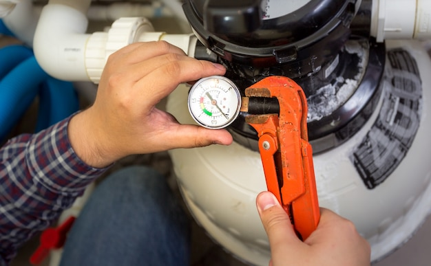 Widok zbliżenia hydraulika instalującego manometr na rurze
