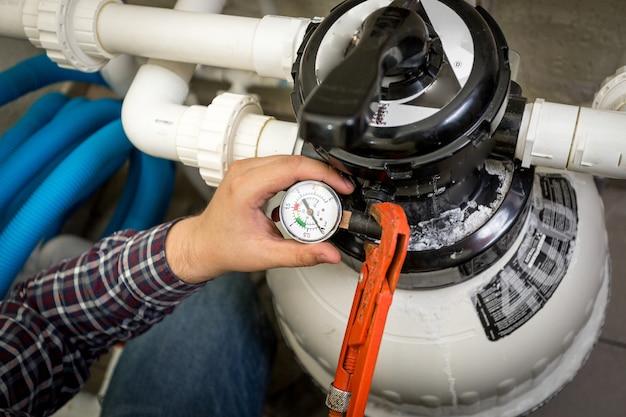 Widok zbliżenia hydraulika sprawdzającego manometr na dużej pompie hydraulicznej