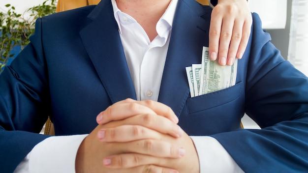 Widok zbliżenia osoby wrzucającej łapówkę do skorumpowanej kieszeni polityka