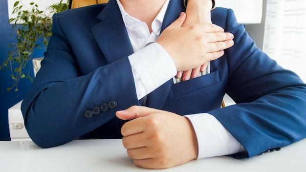 Widok zbliżenia urzędnika przyjmującego łapówkę i wkładającego ją do kieszeni