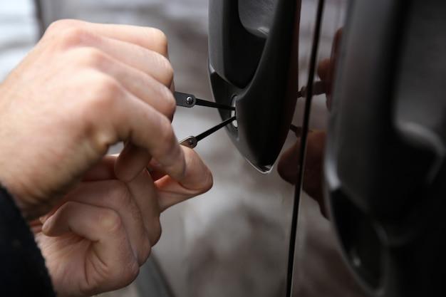 Widok zbliżenie carjacker próbuje otworzyć samochód z wytrychem
