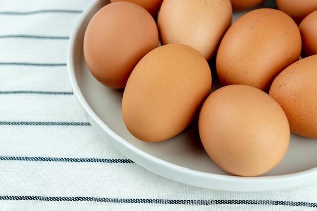 Widok zbliżenie ceramiki płyta pełna wielu surowych całych brązowych jaj kurzych na tle włókienniczych.