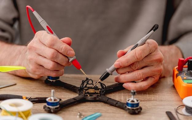 Widok zbliżenie człowieka ręce trzymając urządzenie do sprawdzania doładowania na przewodach quadcopter