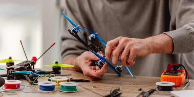 Widok zbliżenie człowieka usługi trzymając się za ręce quadkoptera podczas procesu naprawy