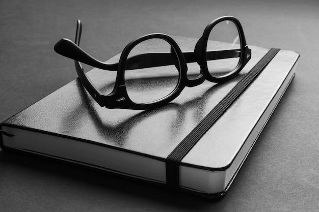 Widok zbliżenie hipster czarne okulary na modny notatnik