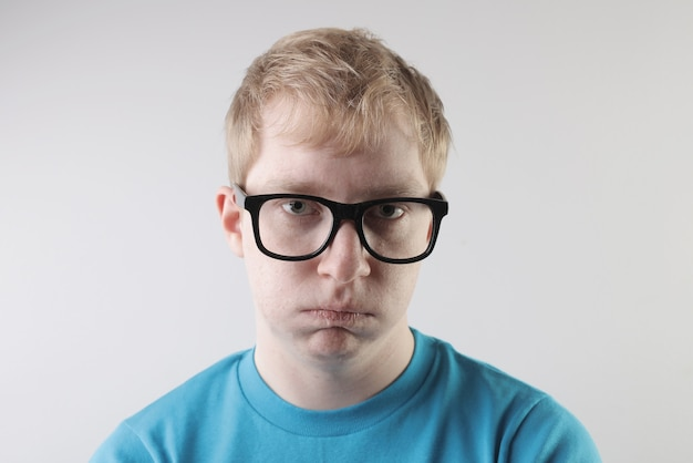 Widok zbliżenie kaukaski mężczyzna ubrany w niebieską koszulkę i okulary, robiąc śmieszne gesty twarzy