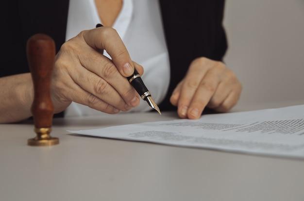 Widok zbliżenie kobiecej ręki trzymającej pióro. papier i pieczęć na biurku.