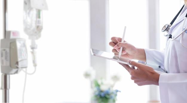 Widok zbliżenie lekarza ręce pisząc na ekranie tabletu z rysikiem, stojąc w pokoju pacjenta.