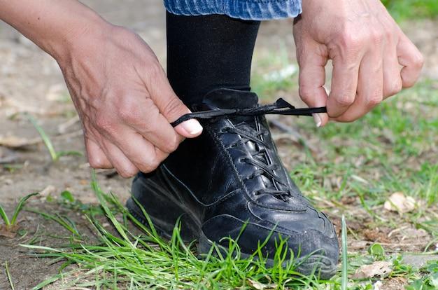 Widok zbliżenie mężczyzny wiązania jego sznurowadło stojąc na trawiastej ziemi