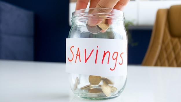 Widok zbliżenie napełniania słoika na oszczędności z monetami.